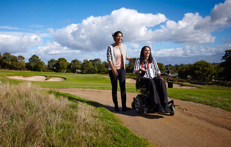 One woman walking one in power wheelchair on golf course