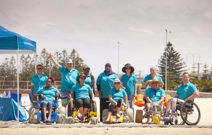 Group shot at the beach with beach wheelchairs